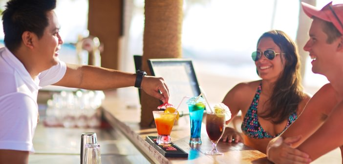Kellner in der Coconut Grove Bar im Bin Majid Beach Resort bedient Paar am Strand