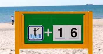 Ein Schild zeigt die Wassertemperatur am Strand an.